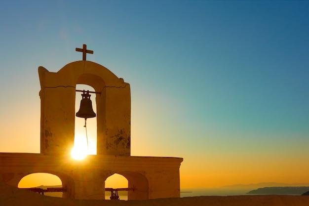 Dzwonnica starego kościoła w mieście thira na wyspie santorini o zachodzie słońca, grecja