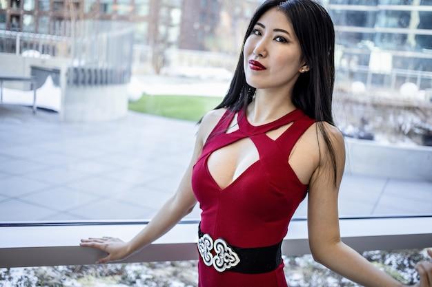 E azjatycki model ubrany w modną elegancką czerwoną sukienkę i błyszczącą czerwoną szminkę