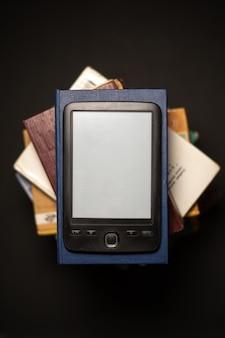 E-book na stosie zwykłych książek papierowych.