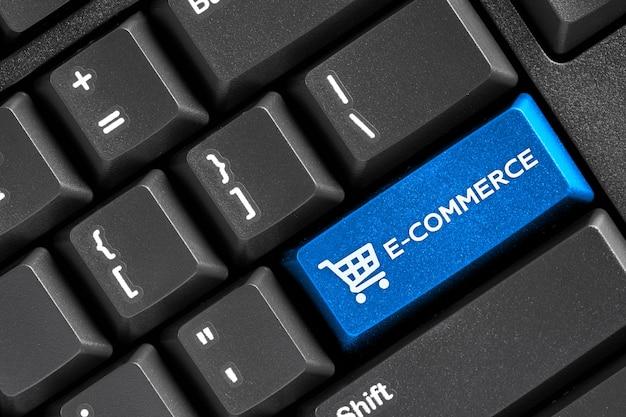 E-commerce słowo niebieski przycisk na komputerze z czarną klawiaturą, koncepcja biznesowa sklepu internetowego