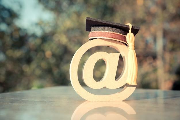 E-learning, online graduation university, na logo poczty znak dla edukacji w zakresie projektowania drewna. świadectwo ukończenia studiów za granicą na międzynarodowych uczelniach może uczyć się na całym świecie dzięki technologii stron internetowych