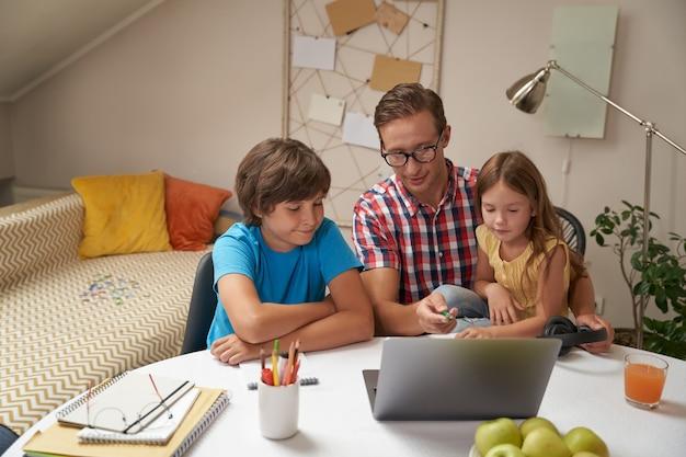 E-learning uroczych małych dzieci z ojcem w okularach, patrząc na syna i córkę laptopa