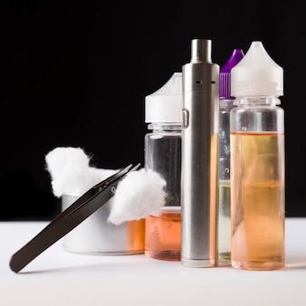 E-liquidy, bawełna, pinceta i elektroniczny cigarrette do vapingu
