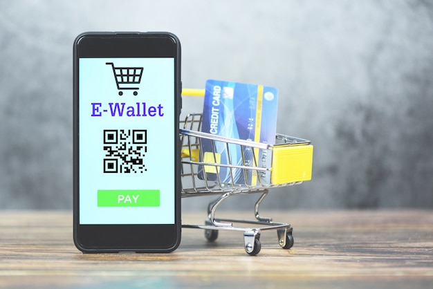 E portfel app na telefonie z kartą kredytową w wózek na zakupy technologii wynagrodzeniu - mobilny płatniczy zakupy online pojęcie