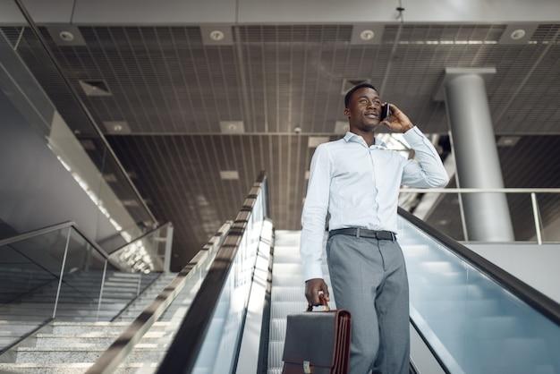 Ebony biznesmen z teczką rozmawia przez telefon na schodach ruchomych w centrum handlowym. sukcesy biznesmena, murzyn w wizytowym, centrum handlowym