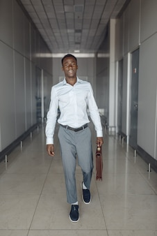 Ebony biznesmen z teczką w hali biurowej. biznesmena sukcesu idąc korytarzem, czarny mężczyzna w wizytowym
