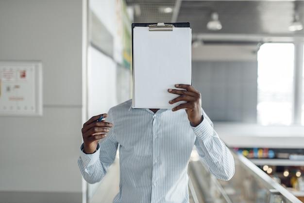 Ebony biznesmen zakrywa twarz notebookiem w centrum handlowym. sukcesy biznesmena, murzyn w wizytowym, centrum handlowym