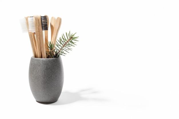 Eco bambusowe szczoteczki do zębów w szarym kamiennym kubku z gałązką jodły na białym tle. skopiuj miejsce.