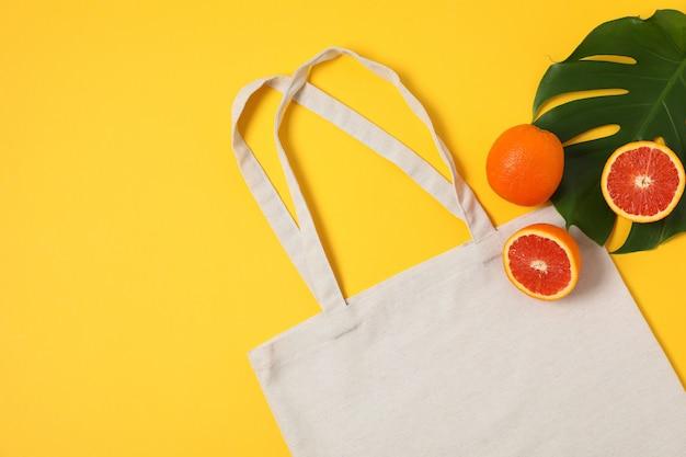 Eco torba, liść palmowy i pomarańcze na koloru tle