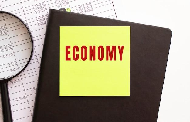Economy tekst na naklejce na pulpicie. pamiętnik i lupa. koncepcja finansowa.