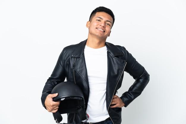 Ecudorian mężczyzna w kasku motocyklowym na białym tle na białej ścianie, pozowanie z rękami na biodrze i uśmiechnięty