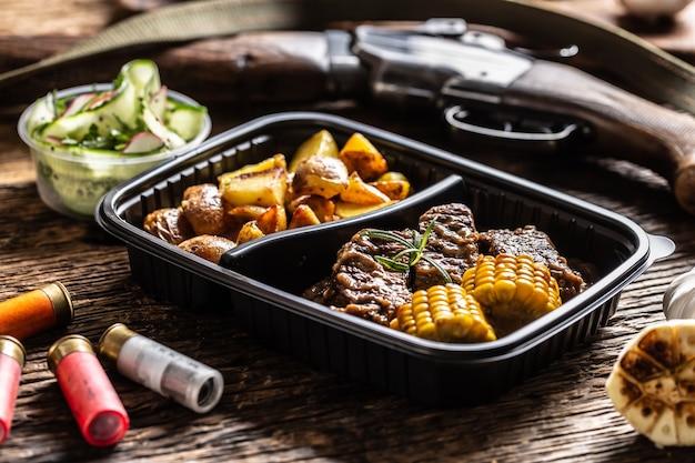 Eddititon myśliwski w przenośnym plastikowym pudełku na wynos składający się z pysznych pieczonych ziemniaków z gulaszem z dziczyzny i kukurydzą. całe jedzenie jest otoczone strzelbą myśliwską i kulami.