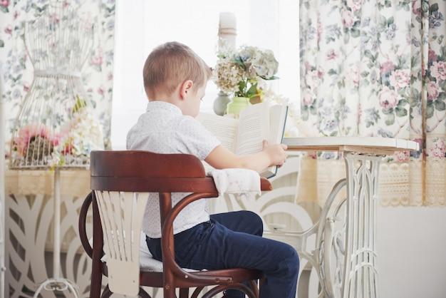 Edukaci, dzieciństwa, ludzi, pracy domowej i szkoły pojęcie, - zanudzająca studenckiej chłopiec czytelnicza książka lub podręcznik w domu