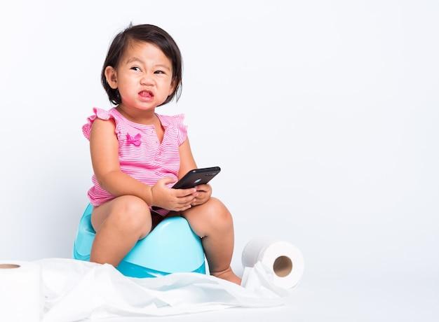 Edukacja Dla Dziewczynki Do Siedzenia Na Nocniczku I Grania Na Smartfonie Premium Zdjęcia