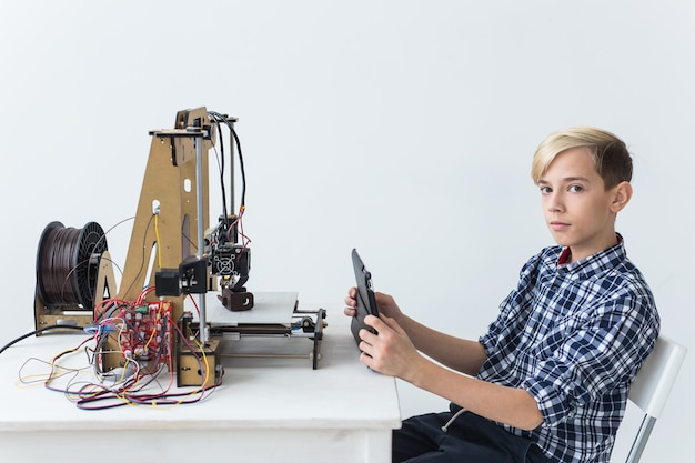Edukacja, dzieci, koncepcja technologii - nastolatek chłopiec drukuje na drukarce 3d.