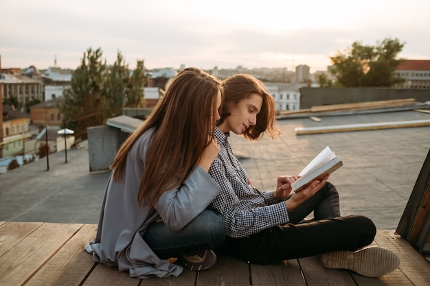 Edukacja i studia. spokojny sposób na poznanie nowych informacji. studenci czytają książkę na dachu