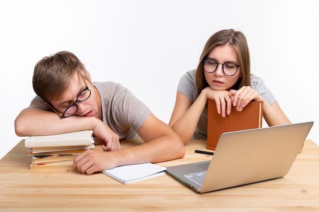 Edukacja, koncepcja ludzi - para młodych ludzi w okularach wygląda jakby byli znudzeni nauką