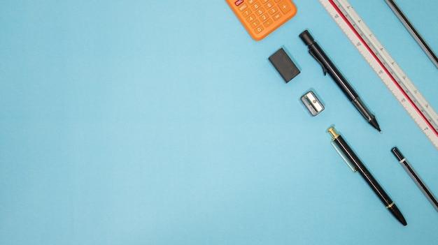 Edukacja lub powrót do koncepcji szkoły. widok z góry na kolorowe przybory szkolne z książkami, kredkami, kalkulatorem, klipsami do obcinania długopisów i jabłkiem na niebieskim pastelowym tle. leżał płasko.