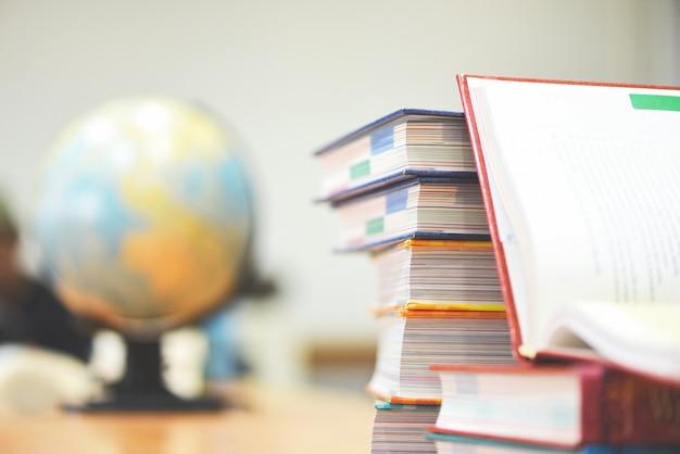 Edukacja lub powrót do szkoły i biznesu studiują globalny świat otwartą książkę w bibliotece z książkami ułożonymi w stos i ziemią