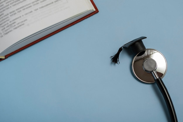 Edukacja medyczna. stetoskop, książka i kapelusz absolwenta. pojęcie medyczne na niebieskim tle. ukończyć