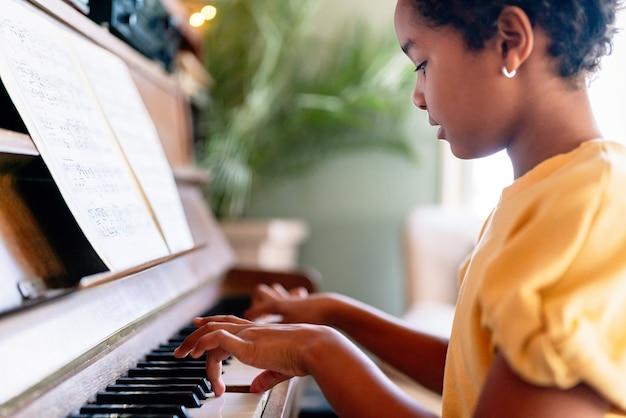 Edukacja muzyczna. szczęśliwa czarna dziewczyna gra na pianinie w domu