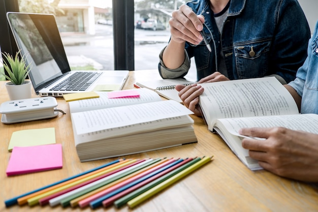 Edukacja, nauczanie, uczenie się, technologia i koncepcja ludzi. dwaj uczniowie szkół średnich lub koledzy z klasy pomagają przyjacielowi w odrabianiu lekcji w klasie, książki nauczyciela z przyjaciółmi