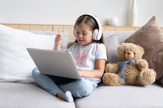 Edukacja online dzieci. słodka dziewczyna ze słuchawkami patrząc wideo lekcja nauczyciel konferencji laptop siedząc na kanapie w domu.
