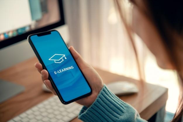 Edukacja online, e-learning. młoda kobieta używa telefon komórkowego z inskrypcją na parawanowym e-learningu i wizerunkiem kwadratowa akademicka nakrętka, szkolenie na odległość.