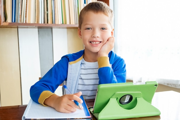 Edukacja online na odległość. chłopiec uczeń patrzy na aparat i uśmiecha się, studiuje w domu z cyfrowym tabletem i odrabia lekcje w szkole. książki szkoleniowe i zeszyty na stole