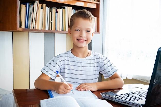 Edukacja online na odległość. chłopiec uczeń patrzy na aparat i uśmiecha się, studiuje w domu z laptopem i odrabia lekcje w szkole. książki szkoleniowe i zeszyty na stole