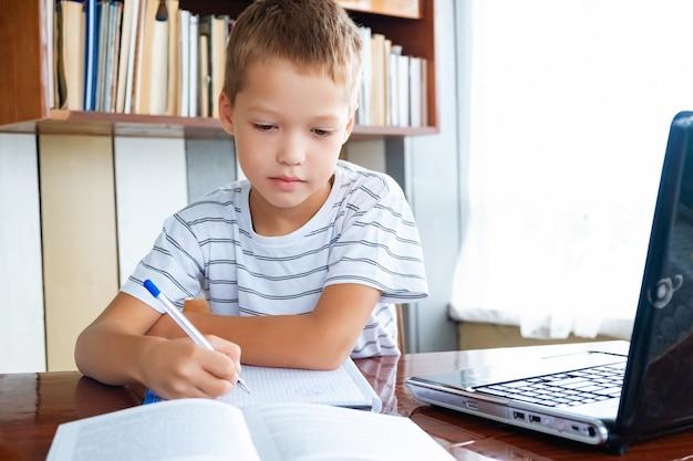 Edukacja online na odległość. chłopiec uczeń studiuje w domu z laptopem i odrabia lekcje w szkole. książki szkoleniowe i zeszyty na stole