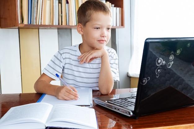 Edukacja online na odległość. kaukaski chłopiec uczy się w domu i odrabia lekcje, pisze w skoroszycie i patrzy na laptopa