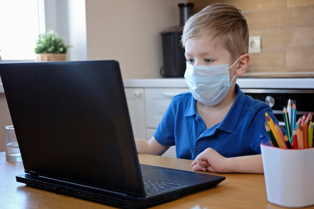 Edukacja online na odległość. śliczna caucasian chłopiec robi pracie domowej na komputerze podczas gdy kwarantanna epidemia korona słoneczna wirus