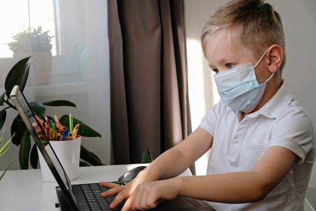 Edukacja online na odległość. śliczna caucasian chłopiec robi pracie domowej z laptopem w domu podczas gdy kwarantanna epidemii korony słonecznej wirus