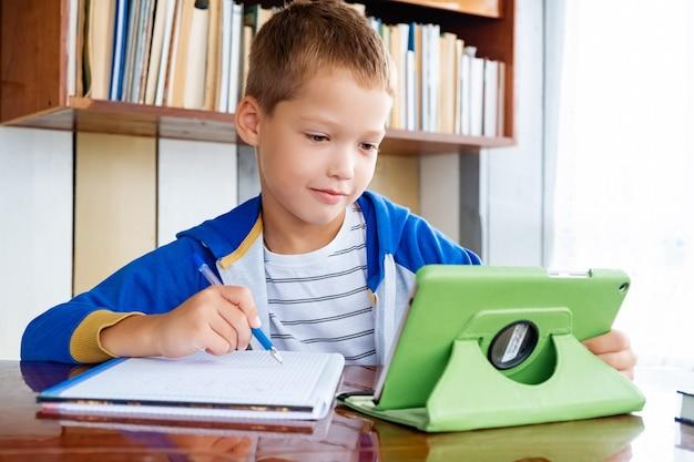 Edukacja online na odległość. uczeń chłopiec studiuje w domu z cyfrowym tabletem i odrabia lekcje w szkole. książki szkoleniowe i zeszyty na stole.