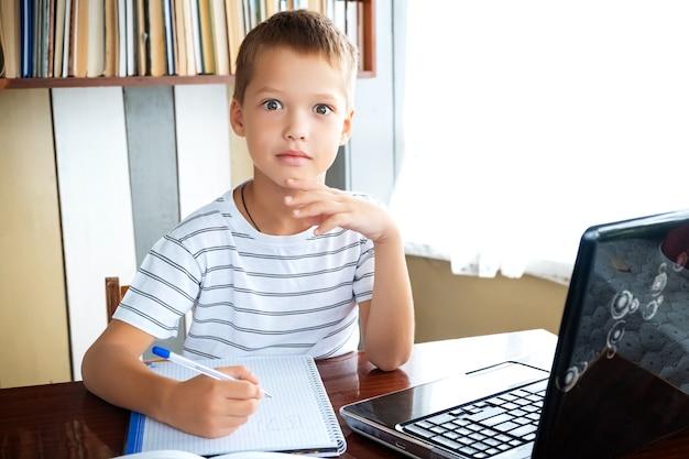 Edukacja online na odległość. uczeń chłopiec ze zdziwioną, zszokowaną twarzą studiuje w domu z laptopem i odrabia lekcje w szkole. książki szkoleniowe i zeszyty na stole.