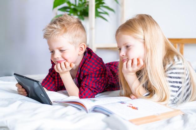 Edukacja online na odległość. uczeń i dziewczyna studiuje w domu z cyfrowym pastylka laptopu notatnikiem i robi szkolnej pracie domowej. siedząc na łóżku z książkami szkoleniowymi.