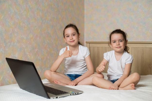 Edukacja online na odległość. uczennica i jej siostra studiuje w domu z cyfrowym notebookiem na laptopa