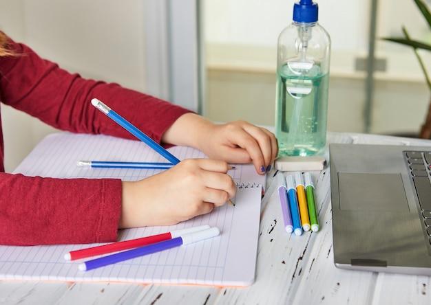 Edukacja online na odległość. uczennica studiuje w domu z laptopem i odrabia lekcje w szkole. książki szkoleniowe i kolorowe flamastry na stole, żel z alkoholem 70 procent