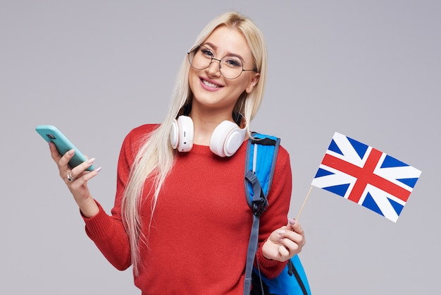 Edukacja online, tłumacz języka obcego, angielski, student - uśmiechnięta blond kobieta w słuchawkach trzyma telefon komórkowy i flagę brytyjską. szara przestrzeń, kształcenie na odległość
