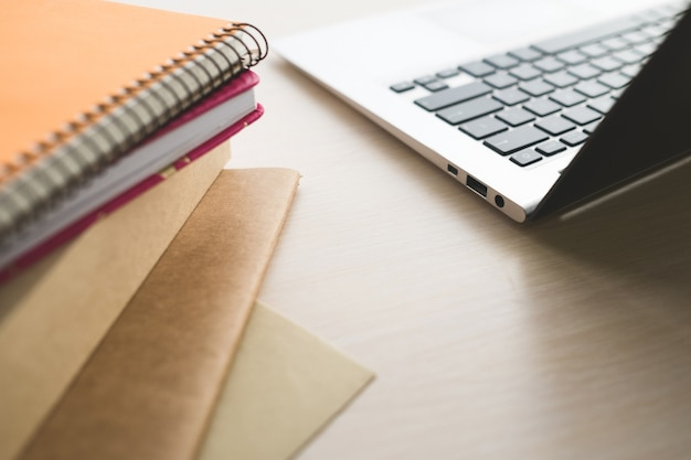 Edukacja online - zdobądź dyplom w internecie. książki, notatniki i laptop na stole.