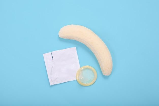 Edukacja seksualna z bananem i prezerwatywą na niebieskim tle