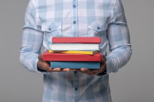 Edukacja. silne, opiekuńcze dłonie ciemnoskórego mężczyzny w kraciastej koszuli, trzymającego podręczniki, jego twarz nie jest widoczna