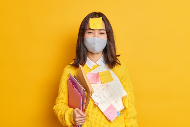 Edukacja społeczna koncepcja dystansu i samoizolacji. azjatycki student uniwersytetu nosi ochronną maskę na twarz podczas koronawirusa nosi foldery i naklejki z notatkami, przygotowując się do końcowego egzaminu z domu