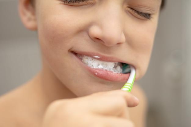 Edukacja stomatologiczna w rodzinie, chłopiec z radością 10 lat, mycie zębów pastą i szczoteczką w łazience