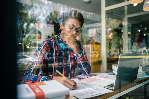 Edukacja szkolna. poważny, rozważny uczeń robi notatki, koncentrując się na swoim zadaniu