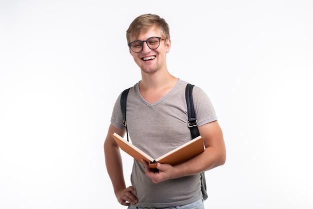 Edukacja, uniwersytet, koncepcja ludzi - student w okularach otworzył książkę i uśmiechał się dalej