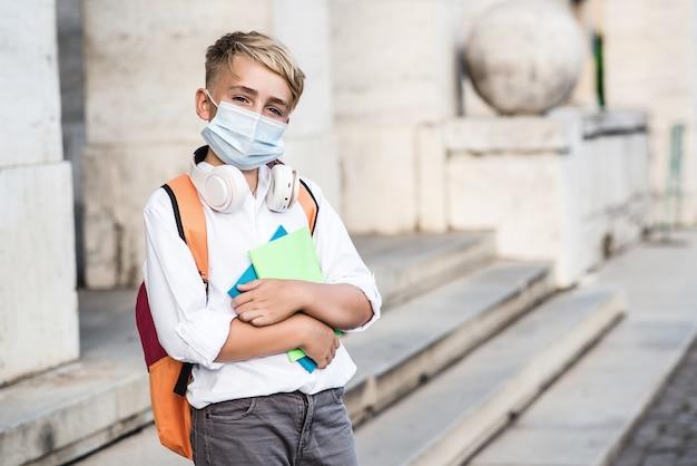 Edukacja w czasie pandemii. chłopiec w szkole noszący maskę podczas epidemii wirusa koronowego. chłopiec wraca do szkoły po kwarantannie covid-19. chłopiec w masce ochronnej do zapobiegania koronawirusowi.