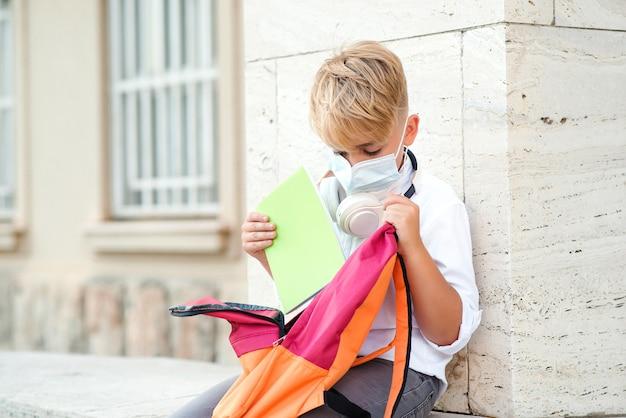 Edukacja w czasie pandemii. zmęczony chłopiec w masce ochronnej po lekcjach. koronawirus a życie szkolne.
