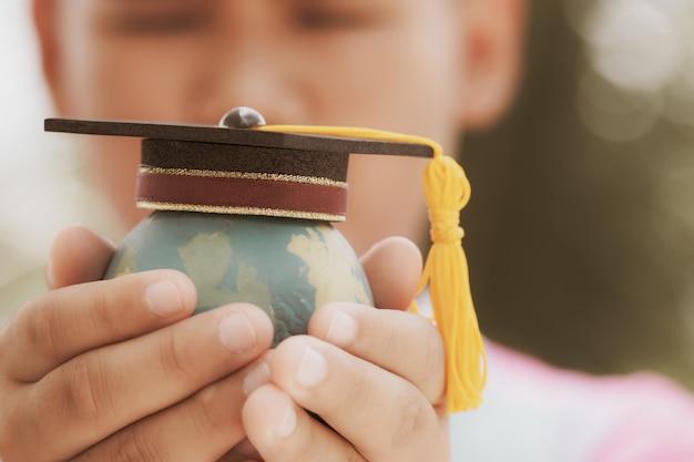 Edukacja w global, graduation cap na topowym modelu ziemi w rękach studenckich.